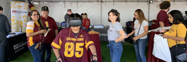IgnitED Labs student worker and visitors watch a kid wearing VR goggles.