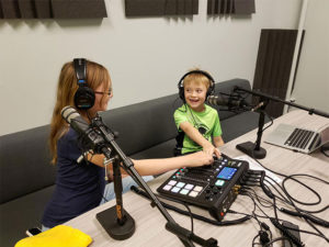 2 kids using the podcasting mixing board and microphones