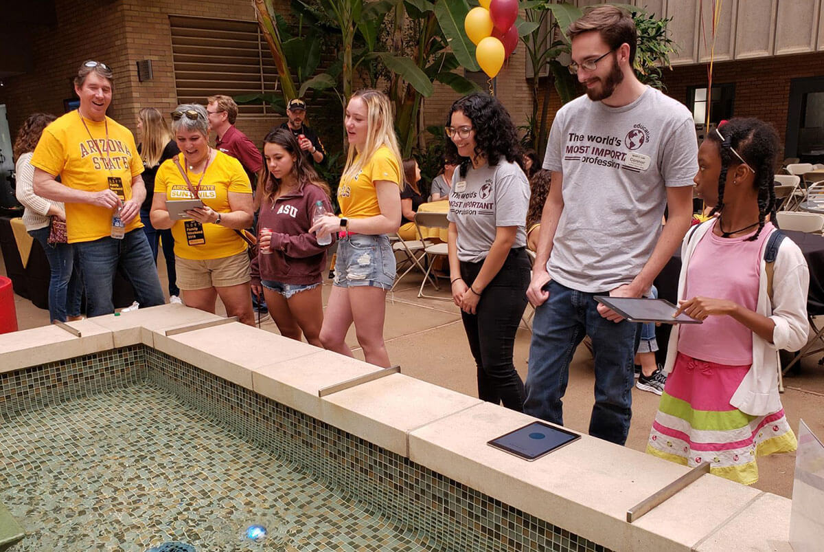 IgnitED staff looks on as visitors control Sphero robots in the water.