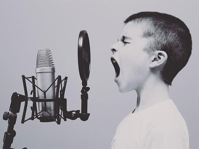 A kid shouting into a microphone