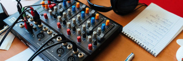 A table in a podcast studio with a notepad, mixing board and headphones